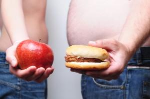 chudý drží jablko a tlstý drží hamburger